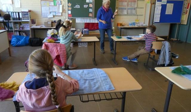 Lehrerin zeigt Kinder einen Filzball