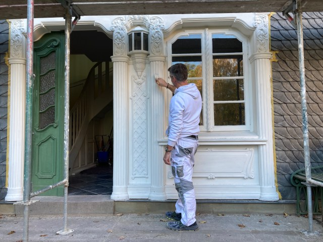 Ein Maler streicht die Verzierung am Hauseingang.