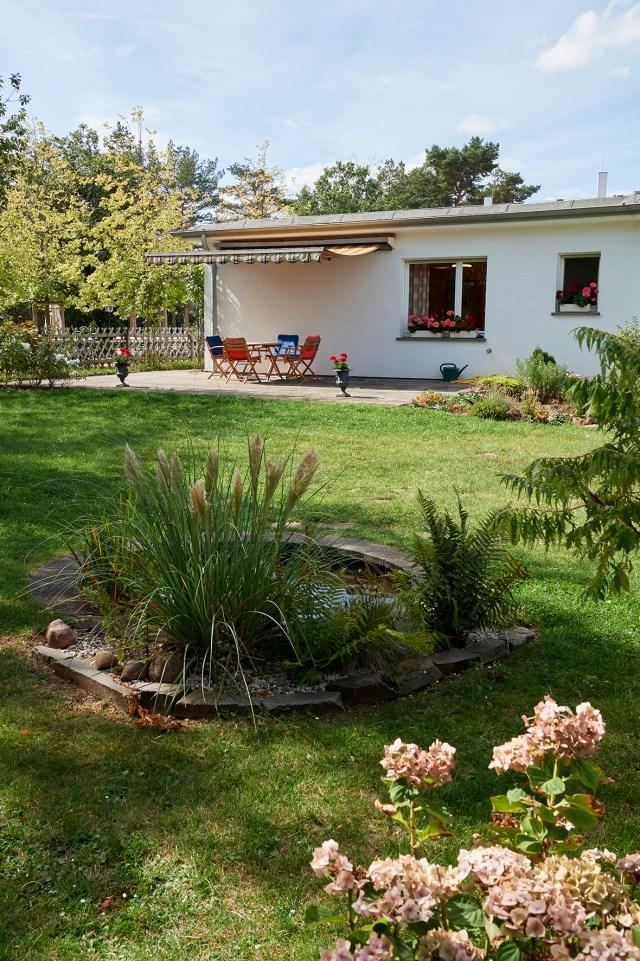Blick in den Garten mit Rasenfläche und kleinem Teich