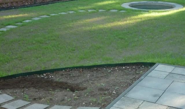 Teil des Gartens mit Wegeplatten und Teich