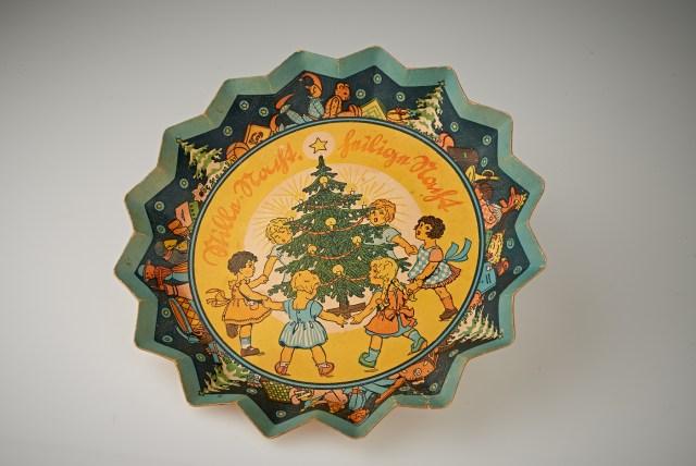 Pappteller in Form eines Sterns mit einem Bild von Kindern, die um einen Weihnachtsbaum tanzen.