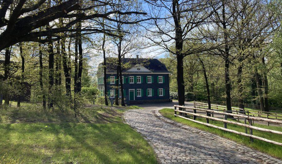 der gepflasterte Weg führt zum grau geschieferten Haus Mannesmann, mit seinen weißen Fenstern und grünen Festerläden.