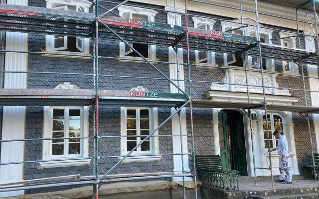 Das Haus Mannesmann mit einem Gerüst, an der Tür steht ein Maler und streicht einen Pilaster