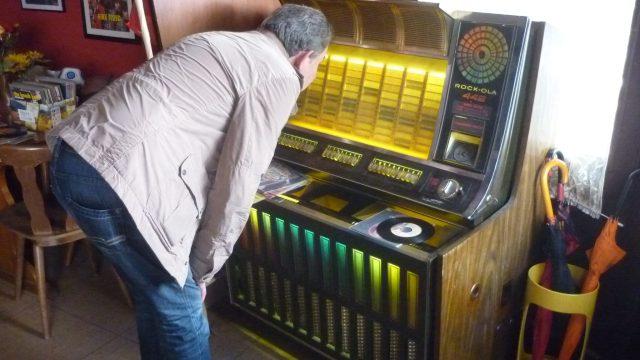 Jukebox, davor ein Mann, der die Titel liest.