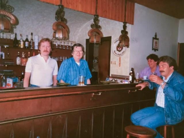 Historisches Foto mit braun getäfelter Theke und Menschen vor und hinter der Theke