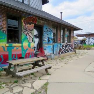Outdoor dining in the arts district beneath creepy murals