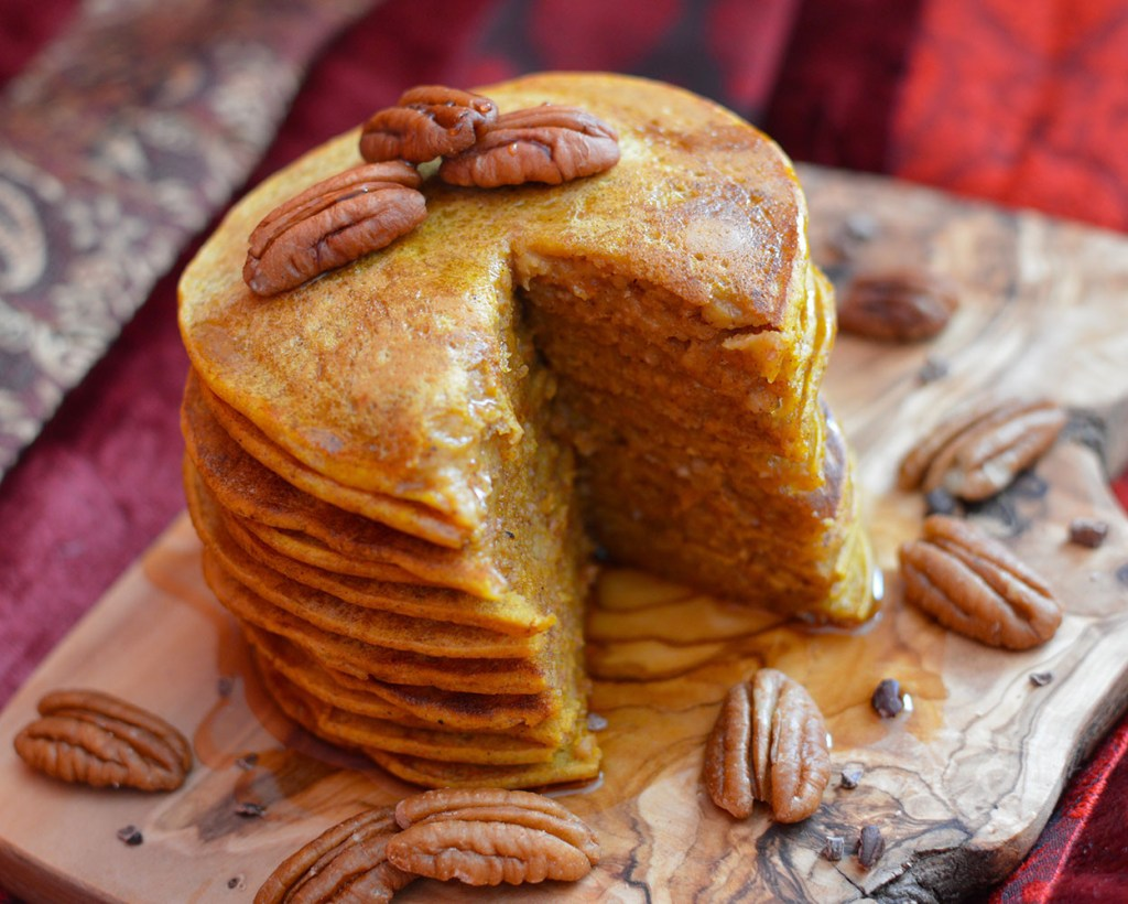 Pumpkin pie pancakes, served with maple syrup and pecans.