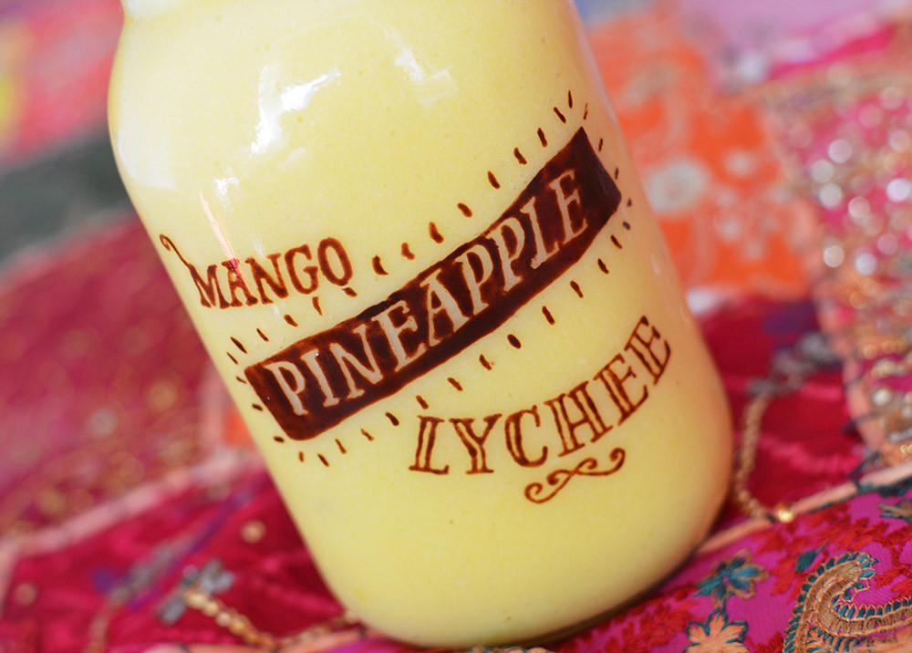 Sweet and zesty, pineapple, mango and lychee tropical smoothie. The writing is painted in raw chocolate.