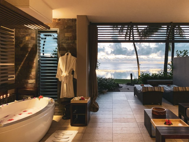 A bubble bath with flowers with a view of the ocean