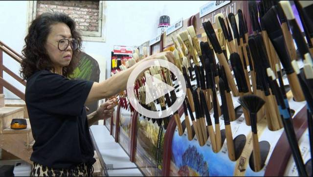 Celia organizing brushes in a screen grab from the news segment.