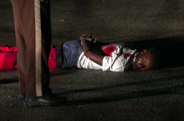 This August 9, 2015 image from video shows a suspect lying on the ground in handcuffs after being shot by police during violence following a day of remembrance for a black teen killed a year earlier in Ferguson, Missouri. Police shot and critically wounded a man who opened fire at them in the US city of Ferguson on Sunday, ending what had been a day of remembrance for a black teen killed a year earlier. The violence came after hundreds of peaceful protesters took to the streets of the St. Louis suburb to mark one year since a white Ferguson officer fatally shot 18-year-old Michael Brown, in an incident that sparked widespread unrest and highlighted persistent racial tensions in America. The latest shooting came after two rival groups exchanged gunfire in the late evening, police said. AFP PHOTO / LOIC HOFSTEDTLOIC HOFSTEDT/AFP/Getty Images