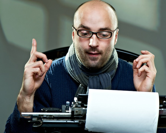 Old fashioned bald writer in glasses writing book on a vintage typewriter