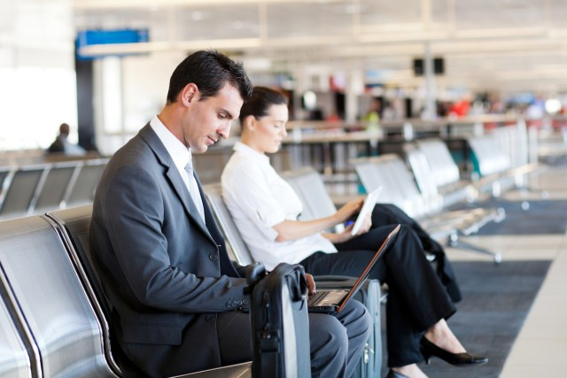 businessman and businesswoman using computer at airport