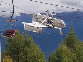an airplane in italy hangs on the wires of a ski lift