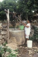 Villager in native huipil drawing water.