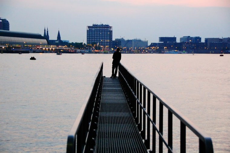 A lone individual at end of a jetty in Amsterdam