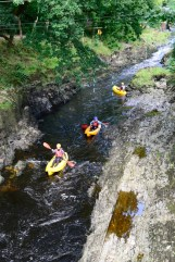 Canoeists on river Teifi beneath gallery balcony
