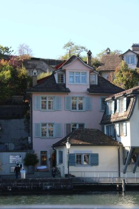 A photo of guild houses in Zurich brown blue and pink architecture from the 1336