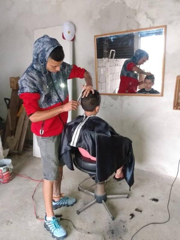 jovem barbeiro no salão improvisado cortando o cabelo