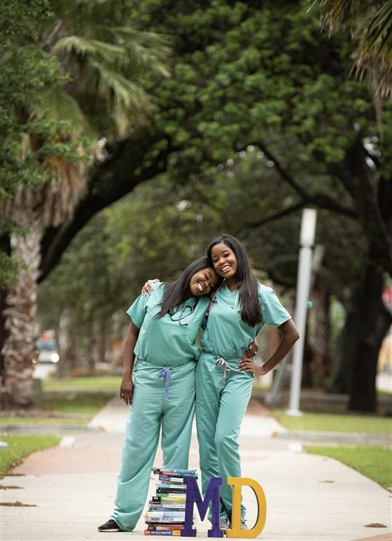 mãe e filha negras com roupas médicas sorrindo