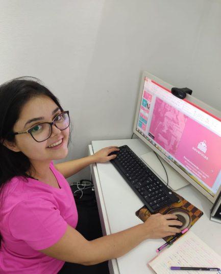 Mulher de camisa rosa e óculos em frente a tela de computador