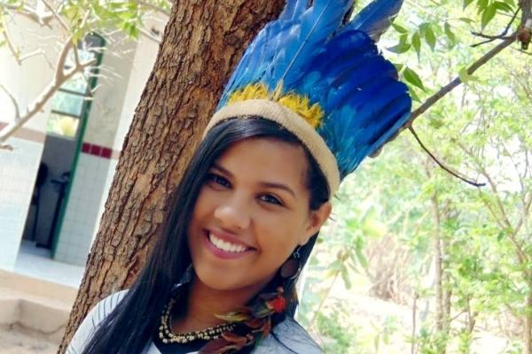 Aluna indígena posa para foto sorrindo de cocar
