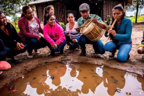 indígenas tocando instrumentos musicais