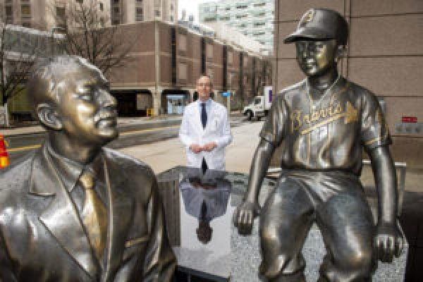 Médico atrás de estátua