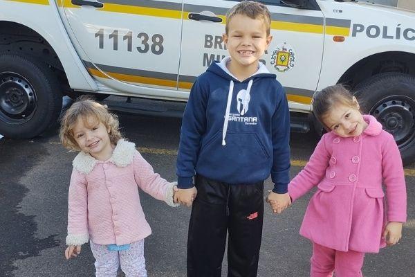 3 crianças com viatura policial ao fundo