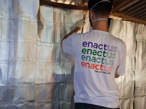homem instala placas caixas de leite parede barraco