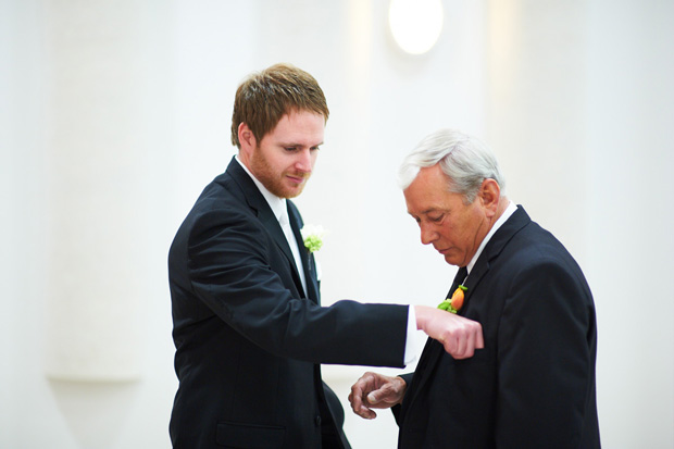 groom adjusting the boutonniere of his father