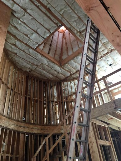 insulated curved walls and raised ceiling with cupola in custom home under construction