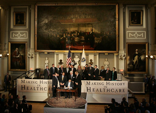 Romney signing RomneyCare into law in MA in 2006