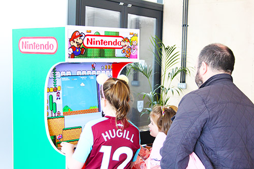 Children playing Arcade Game with Father