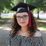 Woman wearing graduation cap looking into camera