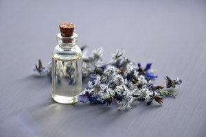 Essential Oils in clear glass bottle next to lavender blooms