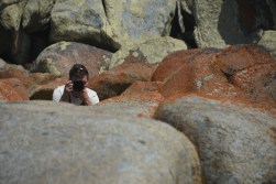 Hayden peeking over the rocks to take a photo of me