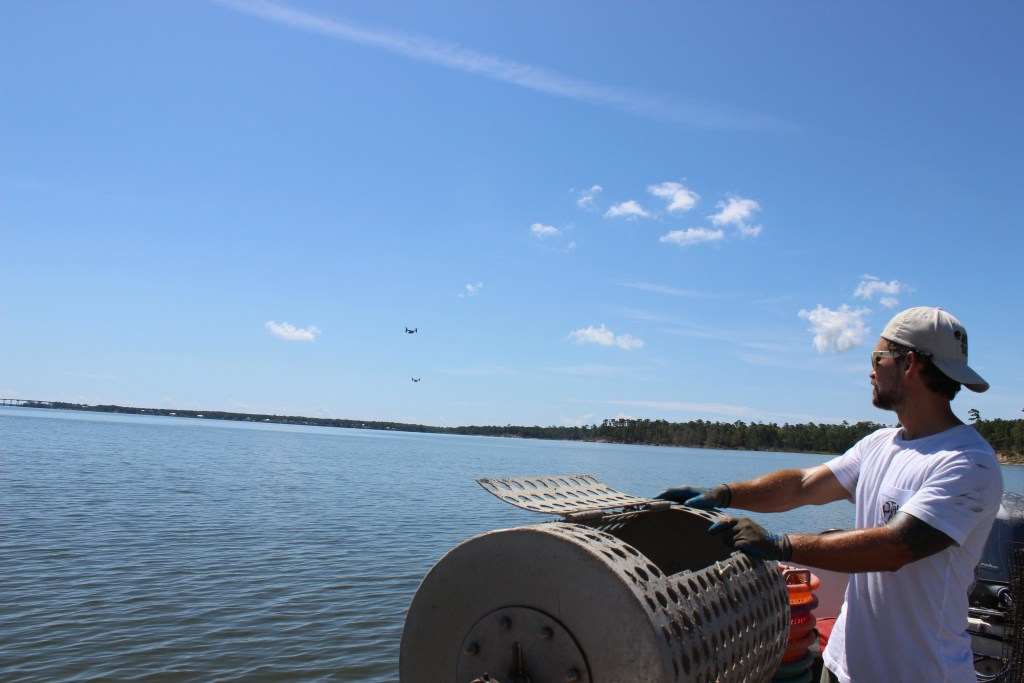 Farmer Matt of Hold Fast Oyster Co in the New River with USMC Osprey's flying overhead.