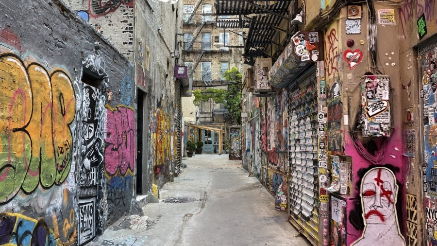 A 3D model of Freeman Alley in New York City's Lower East Side. The walls are covered with colorful graffiti, stickers and posters.