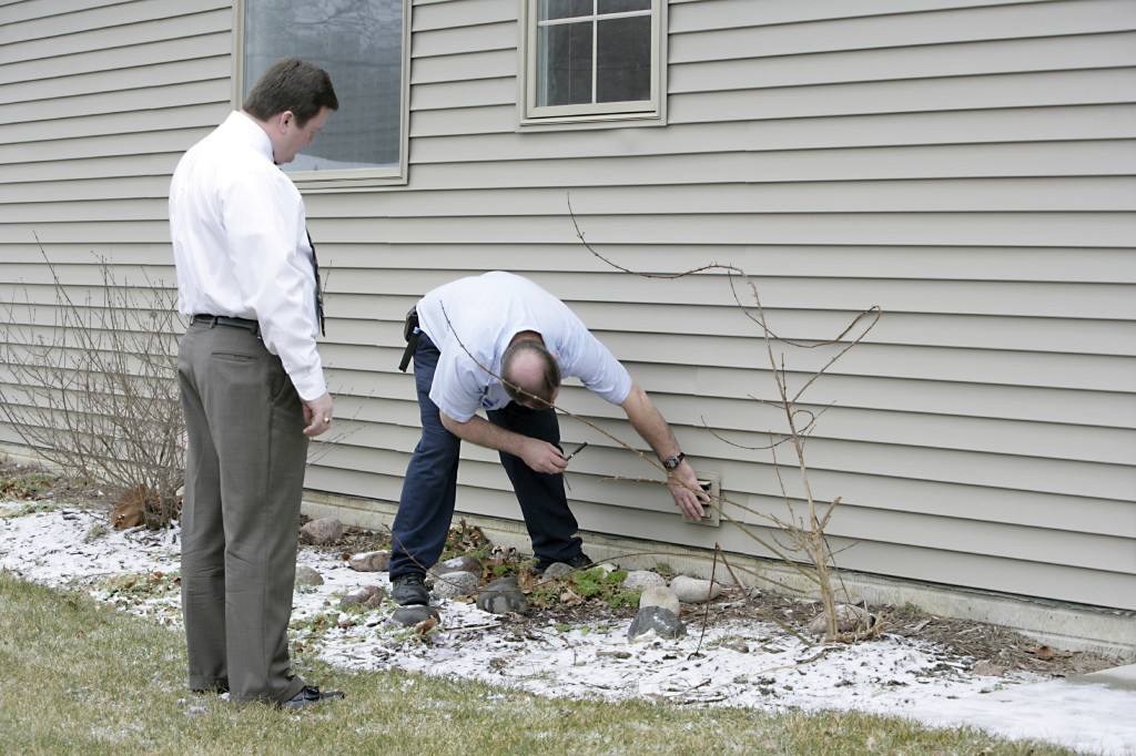 An appraiser checks out the exterior of a house.