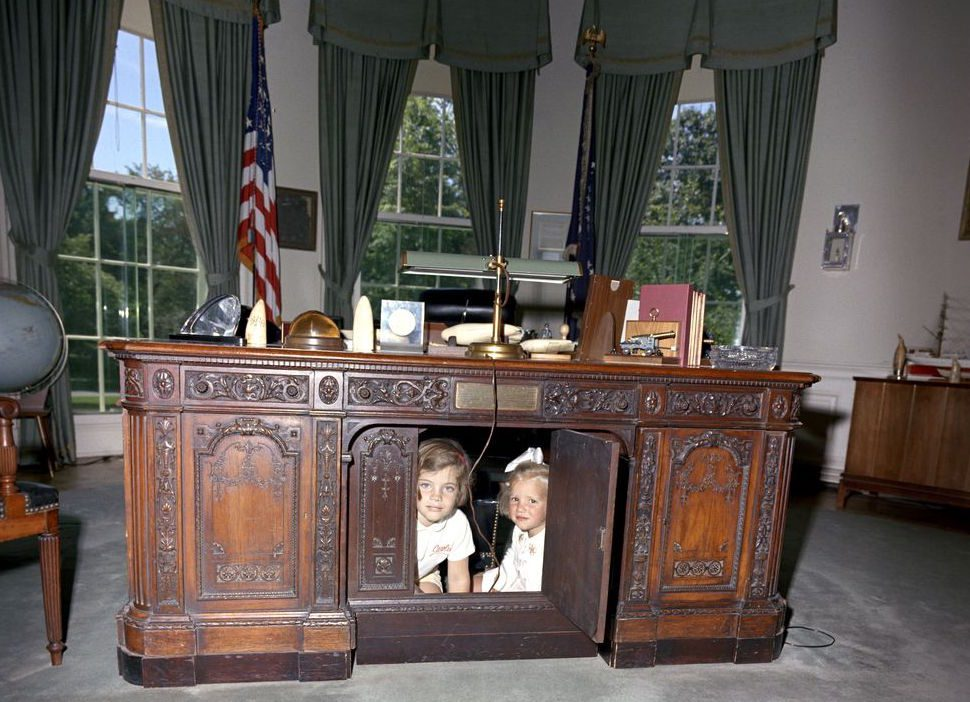 President John F. Kennedy's daughter Caroline and her cousin Kerry under the Resolute desk.