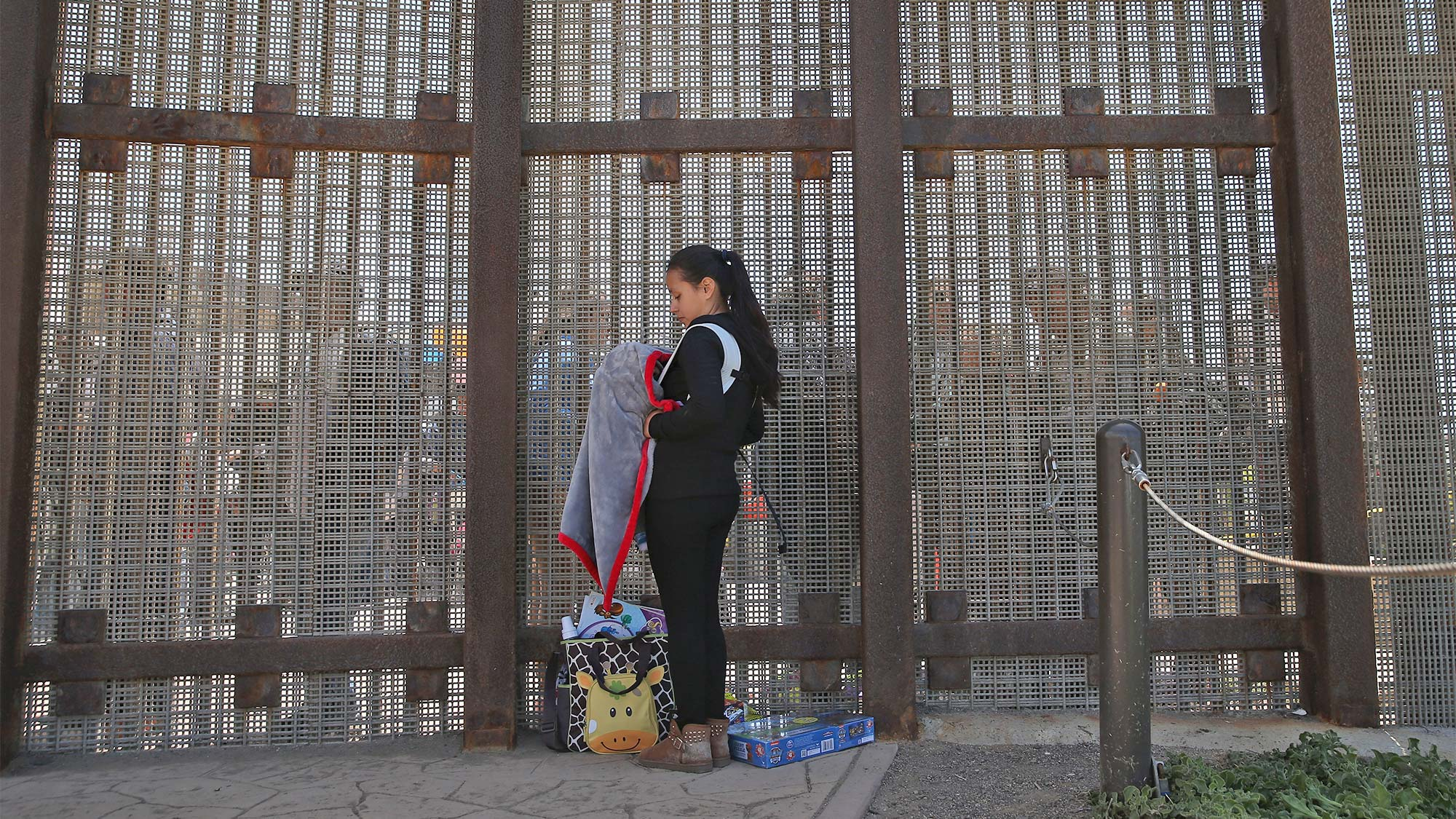 Karen Herrera, 23, holds her baby Ivan, 3 months, while speaking with family members through the U.S.-Mexico border fence.