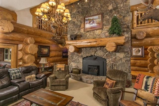 Two-story great rooms and stone fireplaces are common in luxury log cabins