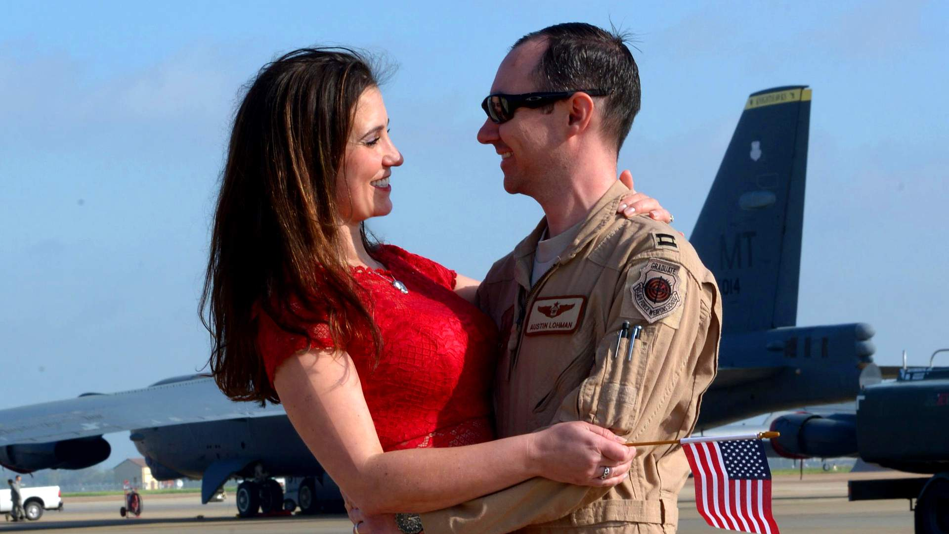 image of an air force pilot hugging his wife he is in his desert brown fatigues and she is wearing a tight red sweater, she is very attractive and very well endowed.