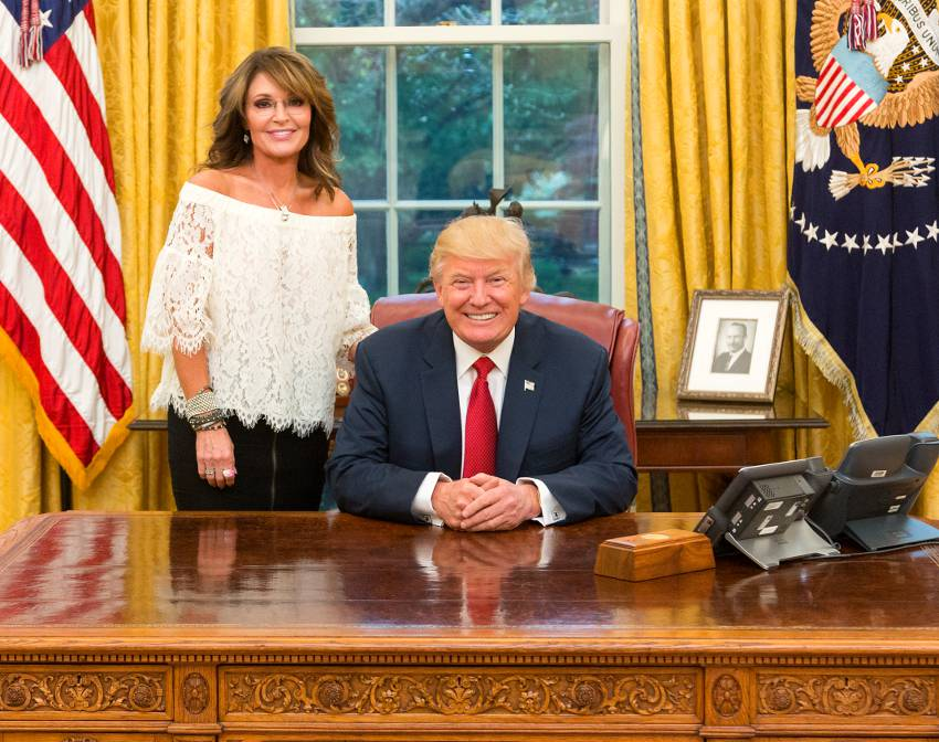 President Trump seated at his desk in the oval office with sarah palin standing on his right, they are both looking at the camera and smiling, sarah looks beautiful with a off the shoulders white blouse and back leather skirt she has long brown hair with blonde streaks with a very slim but curvy figure.