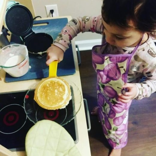 toddler cooking on a grittle