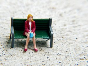 A loenely woman sitting on a bench. This reflects one of the struggles of a stay at home mother.