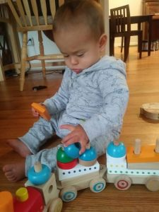 infant playing with wooden train