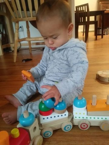 baby playing with wooden train