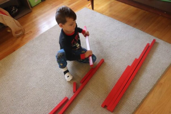 4 year old placing the Montessori Red Rods in order.